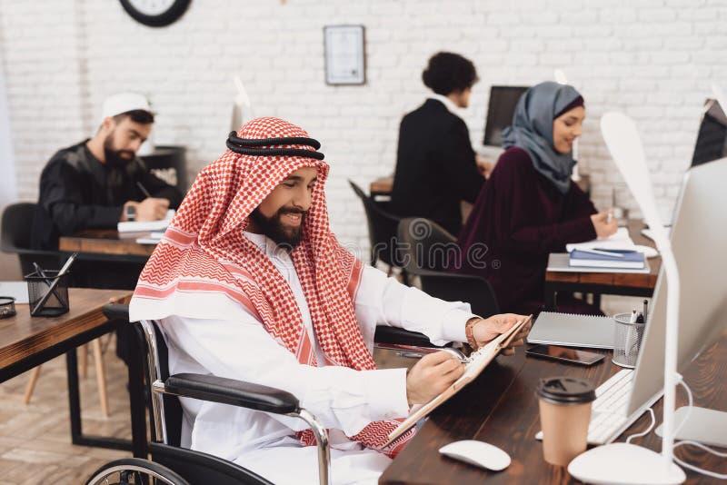Homem árabe deficiente na cadeira de rodas que trabalha no escritório O homem está tomando notas imagem de stock