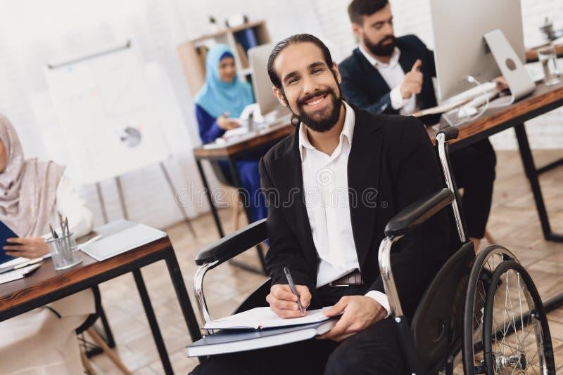 Homem árabe deficiente na cadeira de rodas que trabalha no escritório O homem está tomando notas fotografia de stock