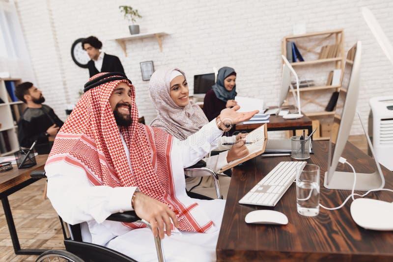 Homem árabe deficiente na cadeira de rodas que trabalha no escritório O homem está tomando notas com colega de trabalho fêmea imagem de stock