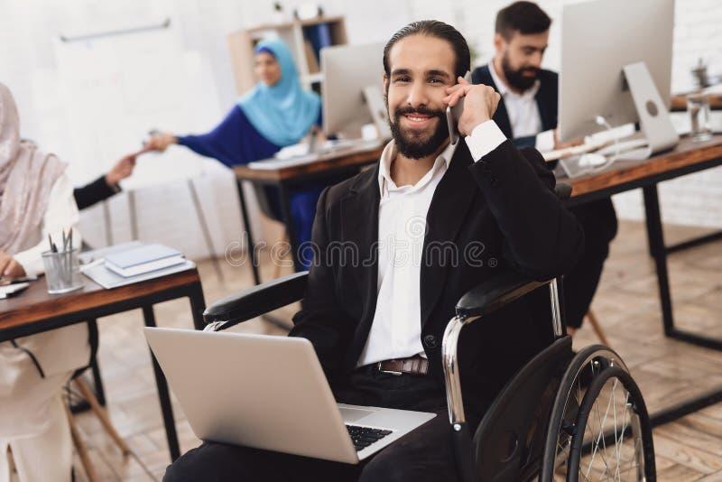 Homem árabe deficiente na cadeira de rodas que trabalha no escritório O homem está trabalhando no portátil imagem de stock royalty free