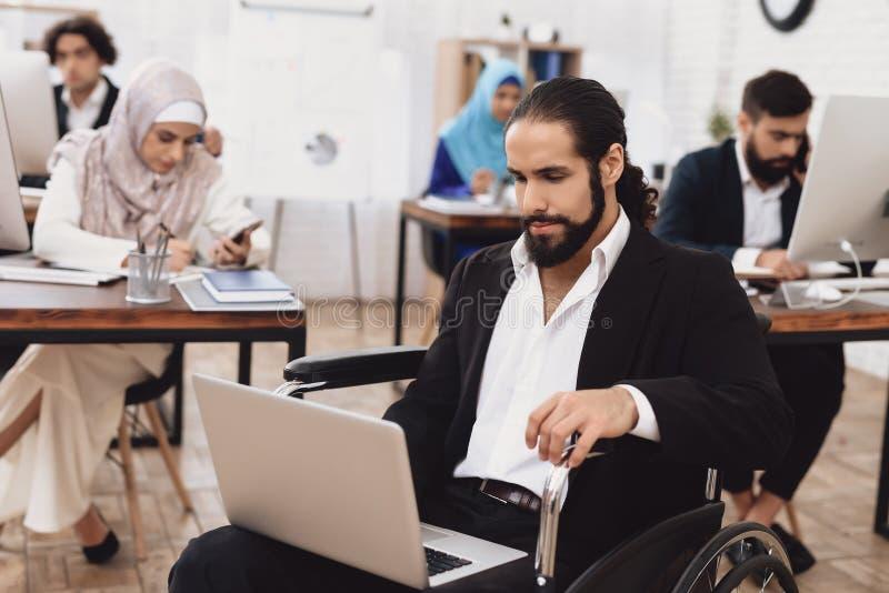 Homem árabe deficiente na cadeira de rodas que trabalha no escritório O homem está trabalhando no portátil imagem de stock