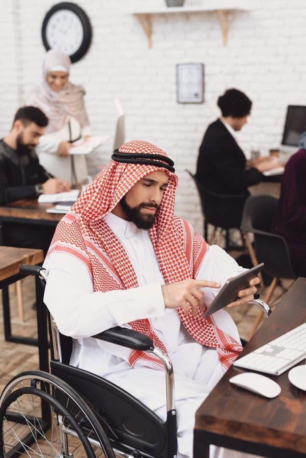 Homem árabe deficiente na cadeira de rodas que trabalha no escritório O homem está usando a tabuleta imagem de stock