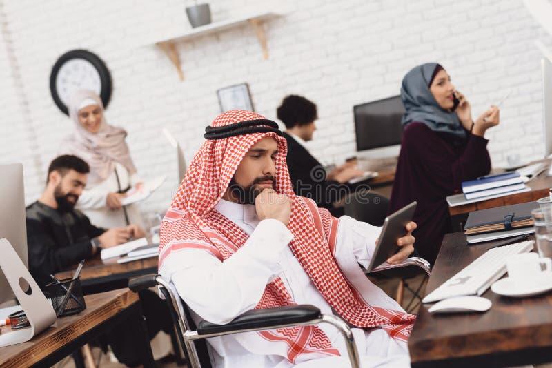 Homem árabe deficiente na cadeira de rodas que trabalha no escritório O homem está usando a tabuleta imagens de stock royalty free