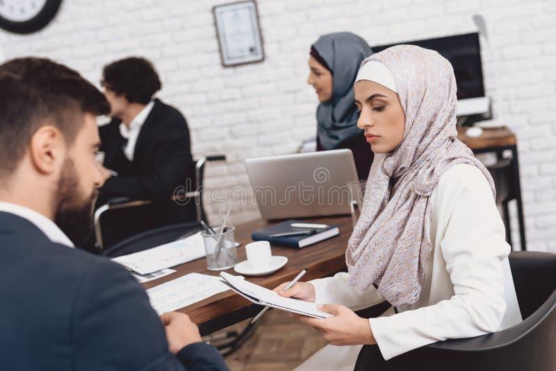 Homem árabe deficiente na cadeira de rodas que trabalha no escritório Os colegas de trabalho estão discutindo notas foto de stock