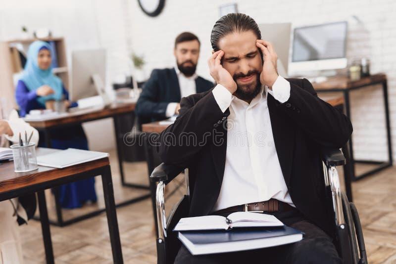 Homem árabe deficiente na cadeira de rodas que trabalha no escritório Os danos da cabeça do ` s do homem fotografia de stock royalty free
