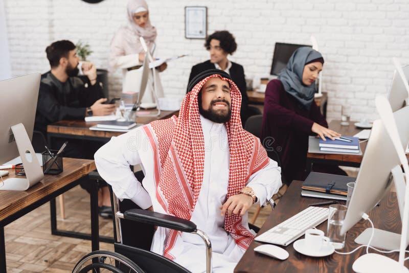 Homem árabe deficiente na cadeira de rodas que trabalha no escritório Os danos da parte traseira do ` s do homem fotografia de stock royalty free