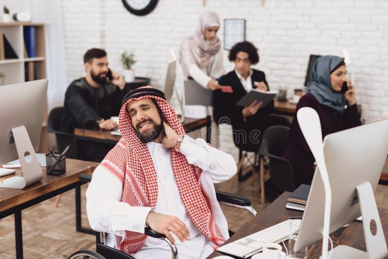Homem árabe deficiente na cadeira de rodas que trabalha no escritório Os danos do pescoço do ` s do homem fotografia de stock royalty free