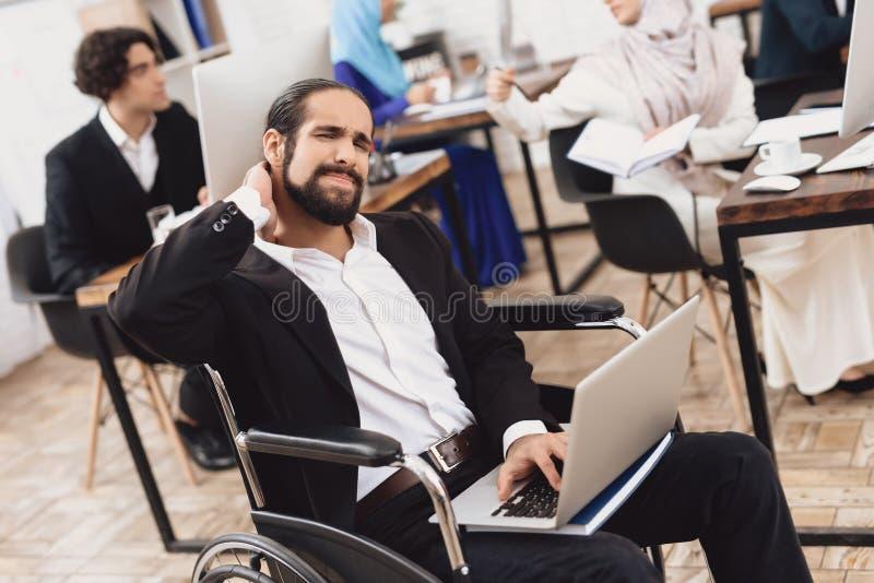 Homem árabe deficiente na cadeira de rodas que trabalha no escritório Os danos do pescoço do ` s do homem foto de stock