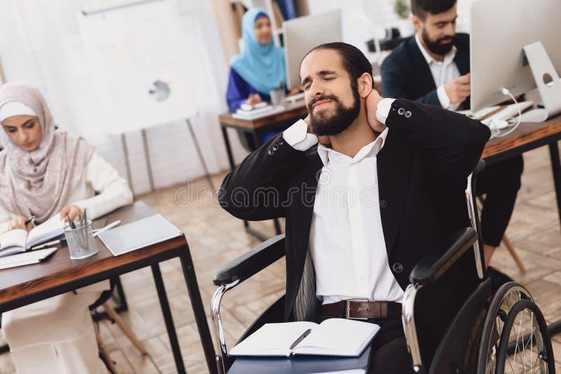 Homem árabe deficiente na cadeira de rodas que trabalha no escritório Os danos do pescoço do ` s do homem imagens de stock royalty free