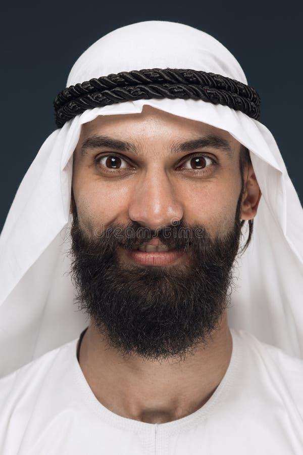 Homem árabe do saudita em escuro - fundo azul do estúdio fotografia de stock royalty free