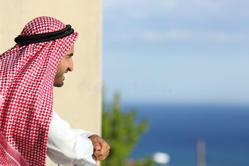 Homem árabe do saudita que olha o mar de um balcão de um hotel foto de stock royalty free