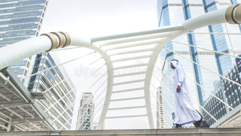 Homem árabe do saudita do viajante do negócio que leva uma mala de viagem e uma caminhada dentro imagens de stock royalty free