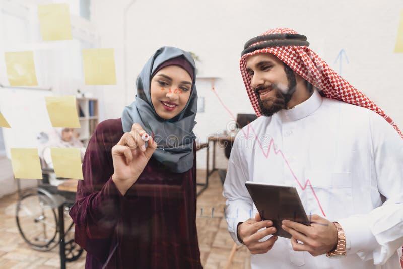 Homem árabe e mulher que trabalham no offce Os colegas de trabalho estão escrevendo notas na placa de vidro imagem de stock royalty free