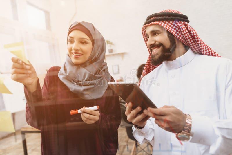 Homem árabe e mulher que trabalham no offce Os colegas de trabalho estão escrevendo notas na placa de vidro fotos de stock royalty free