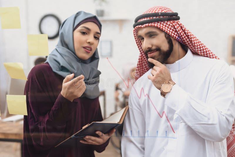 Homem árabe e mulher que trabalham no offce Os colegas de trabalho estão tomando notas na placa de vidro imagem de stock