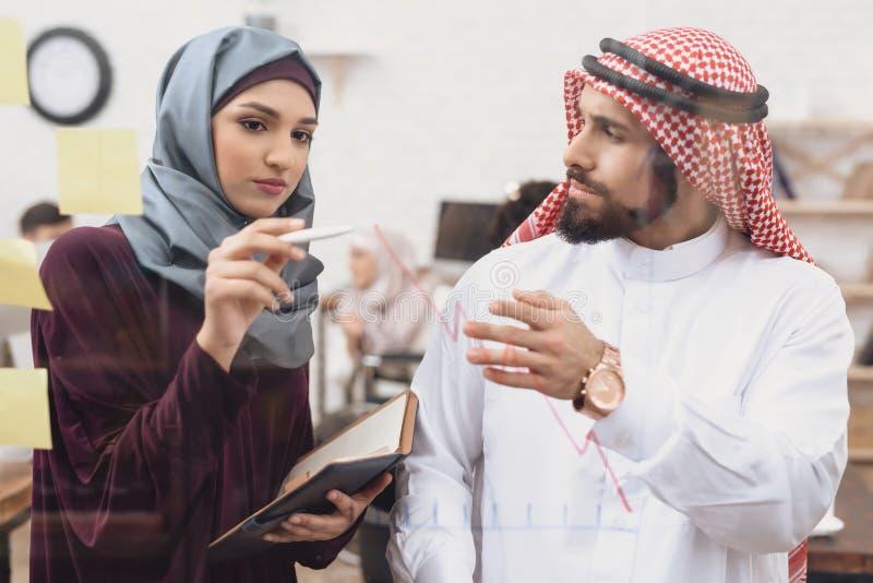 Homem árabe e mulher que trabalham no offce Os colegas de trabalho estão tomando notas na placa de vidro fotografia de stock