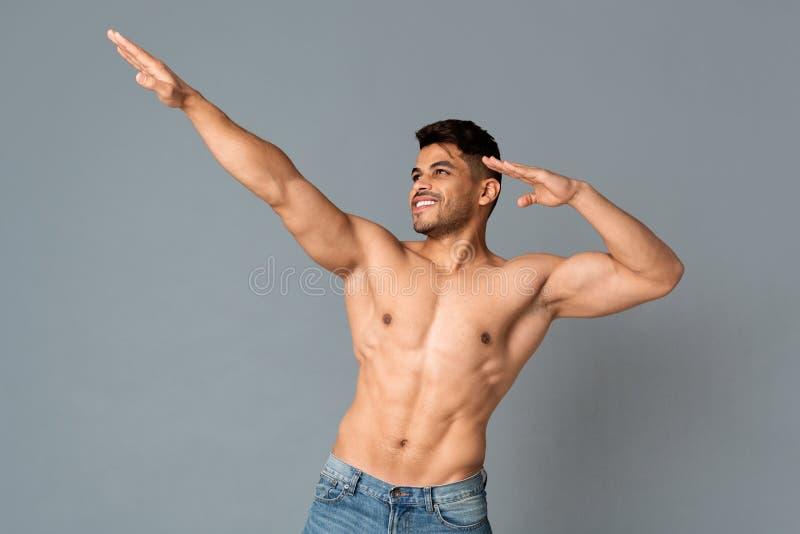 Homem árabe em topless muscular que faz o gesto da dança da solha em Gray Background imagem de stock