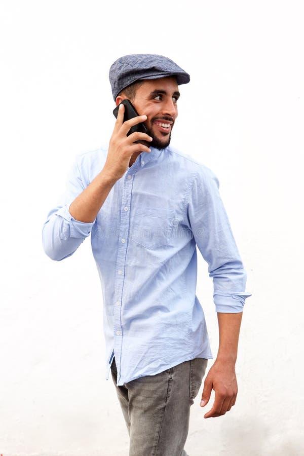 Homem árabe novo fresco que sorri e que fala no telefone celular contra o fundo branco foto de stock royalty free