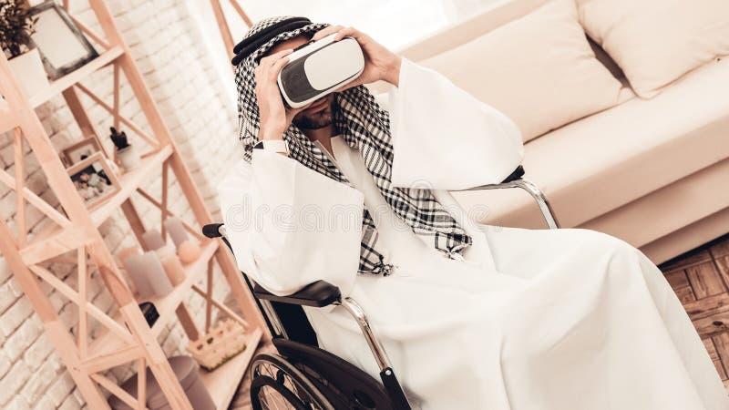 Homem árabe novo na cadeira de rodas usando vidros de VR foto de stock