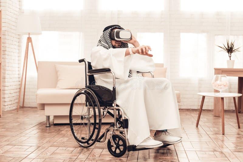 Homem árabe novo na cadeira de rodas usando vidros de VR fotos de stock royalty free
