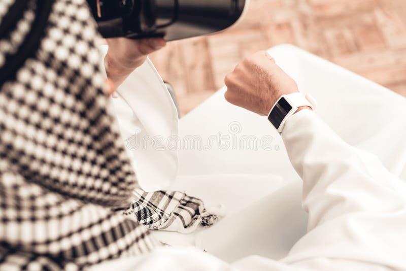 Homem árabe novo na cadeira de rodas usando vidros de VR fotografia de stock