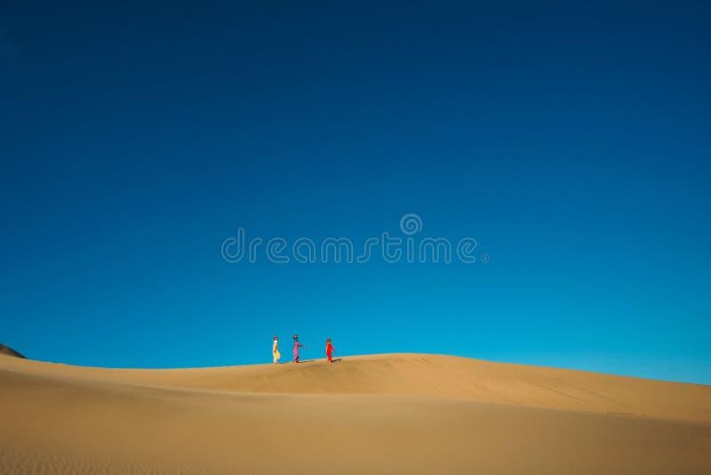Homem ?rabe orgulhoso de Emirati que guarda uma bandeira dos UAE, andando no deserto fotografia de stock royalty free