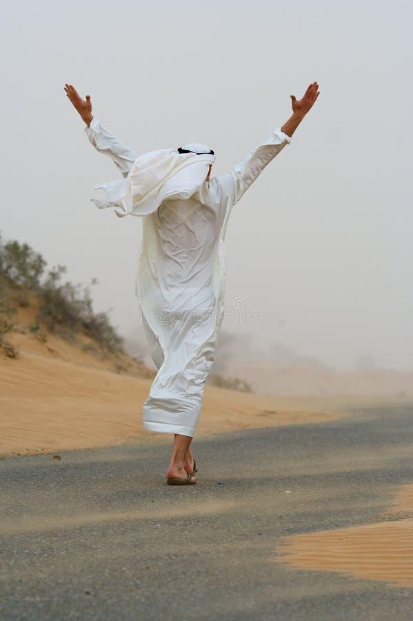 Homem árabe que anda na tempestade de areia fotos de stock