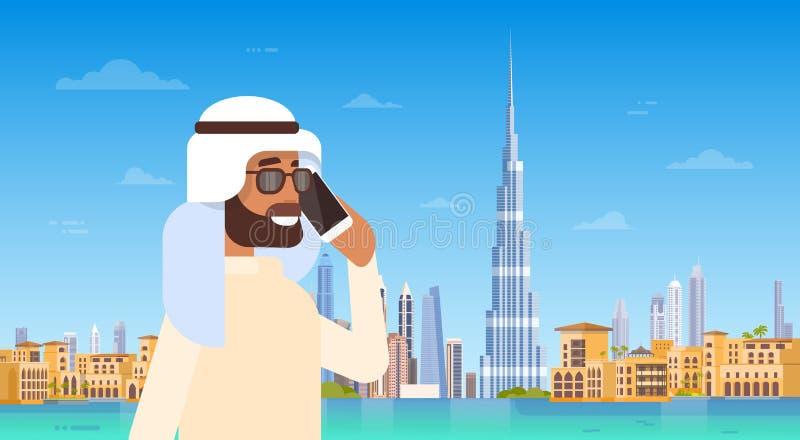 Homem árabe que fala no telefonema esperto da pilha sobre o panorama da skyline de Dubai, arquitetura da cidade moderna da constr ilustração stock