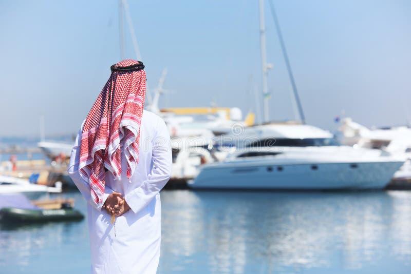 Homem árabe que olha o porto do iate imagem de stock