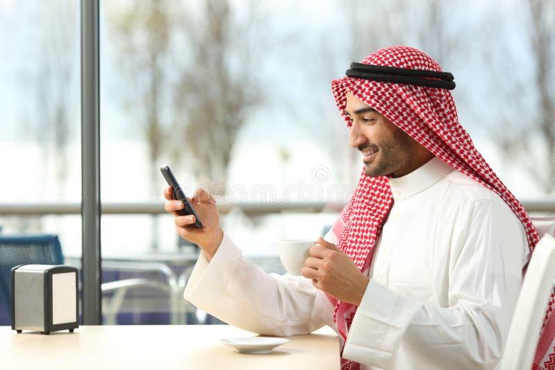 Homem árabe que texting em um telefone esperto em uma barra imagem de stock royalty free