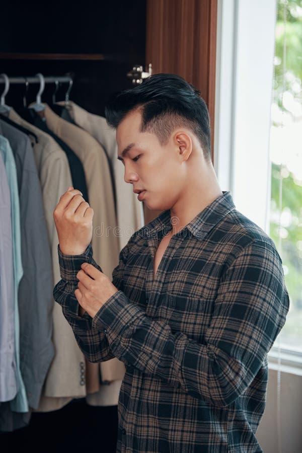 Homem étnico novo que veste-se em casa fotos de stock royalty free