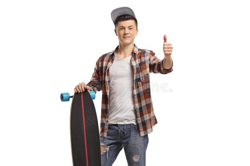 Homem adolescente com um longboard que faz um polegar acima do sinal foto de stock