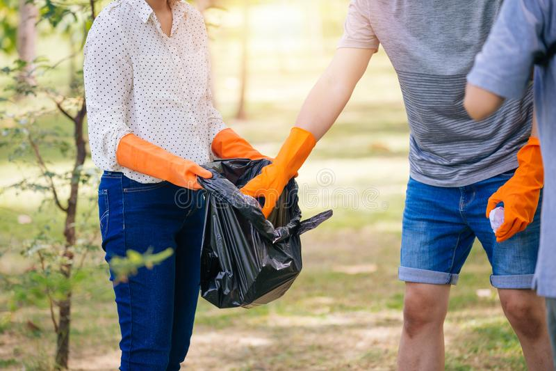 Homem adolescente novo e grupo fêmea de voluntários com luvas que recolhem o desperdício do lixo no saco de lixo no parque verde imagem de stock