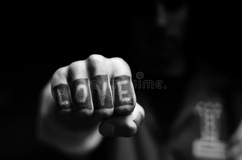 Homem adolescente novo que mostra o texto do amor tattooed em seus dedos fotos de stock