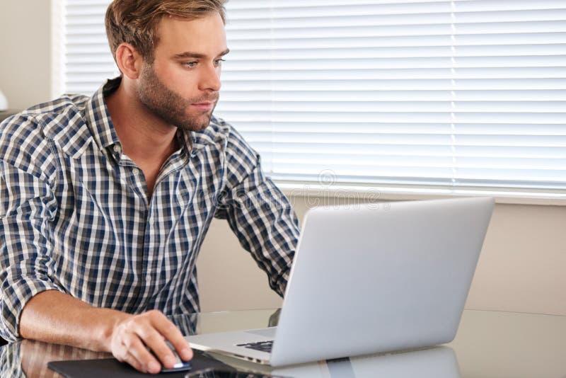 Homem adulto caucasiano novo ocupado usando um portátil e um rato imagem de stock royalty free