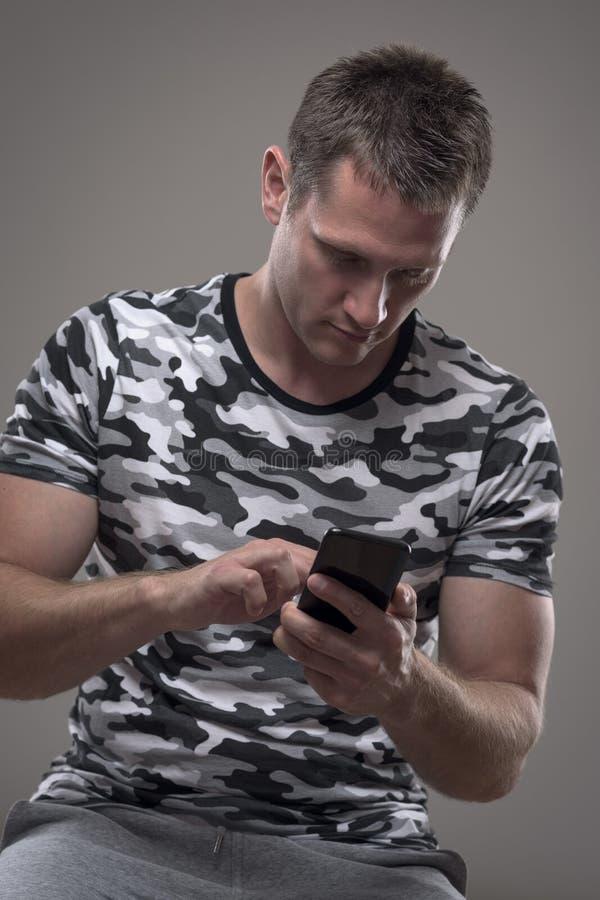 Homem adulto considerável do ajuste novo que usa mensagens de datilografia do telefone celular ou surfando a rede imagens de stock royalty free