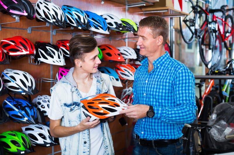Homem adulto e filho que escolhem o capacete bicycling foto de stock royalty free