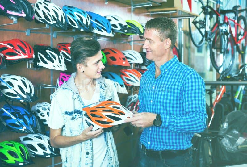 Homem adulto e filho que escolhem o capacete bicycling fotografia de stock