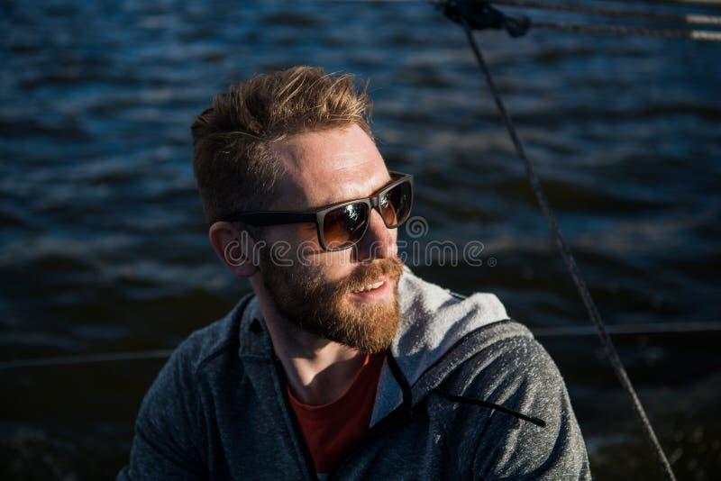 Homem adulto em feliz do retrato do barco do esporte do porto relaxado em um por do sol imagem de stock