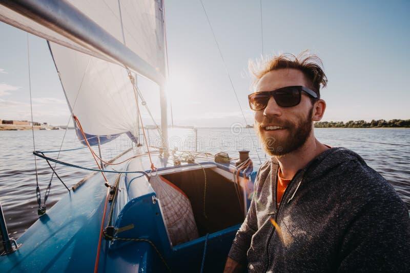 Homem adulto em feliz do retrato do barco do esporte do porto relaxado em um por do sol imagens de stock royalty free