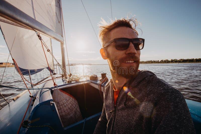 Homem adulto em feliz do retrato do barco do esporte do porto relaxado em um por do sol foto de stock