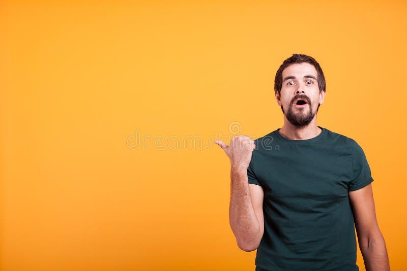 Homem adulto emocional surpreendido que aponta no copyspace fotografia de stock