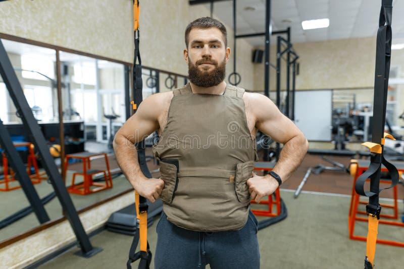 Homem adulto farpado caucasiano muscular do retrato no gym, vestido na veste blindada à prova de balas, esporte militar foto de stock royalty free