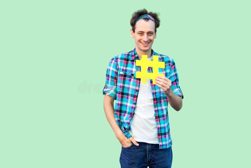 Homem adulto novo otimista contente positivo alegre na camisa quadriculado que guarda o grande sinal amarelo grande do hashtag, c imagem de stock royalty free