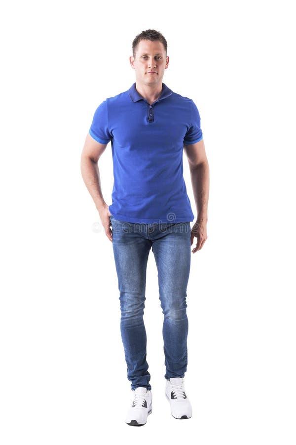 Homem adulto novo relaxado fresco no polo e nas calças de brim que anda e que olha a câmera fotografia de stock