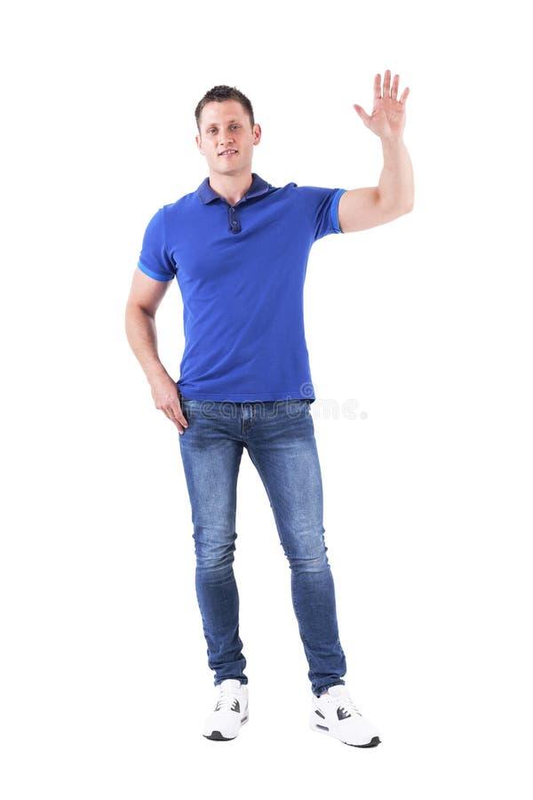 Homem adulto ocasional novo na mão de ondulação e no acolhimento do polo azul olhando a câmera fotos de stock