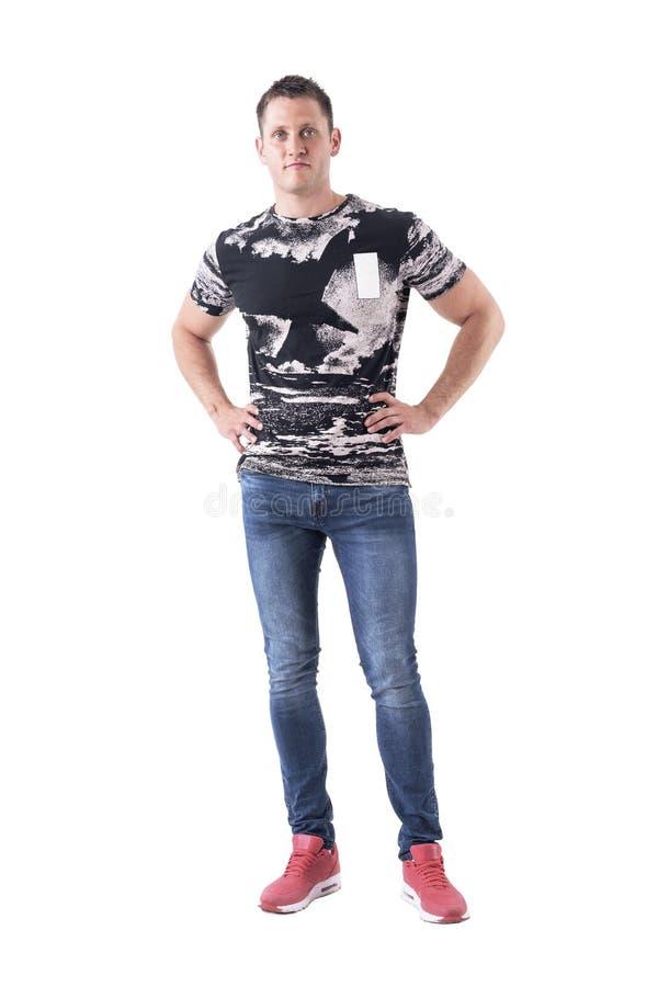 Homem adulto ocasional novo sério nas calças de brim e nas sapatilhas cor-de-rosa que levantam com mãos nos quadris fotos de stock