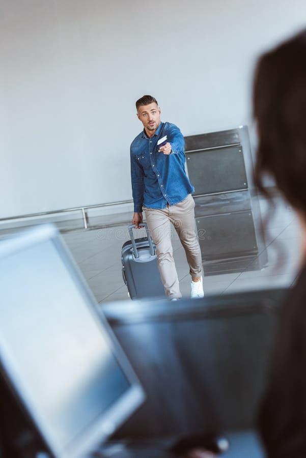 Homem adulto preocupado com o passaporte hurring, outstretching da bagagem e os bilhetes de ar foto de stock royalty free