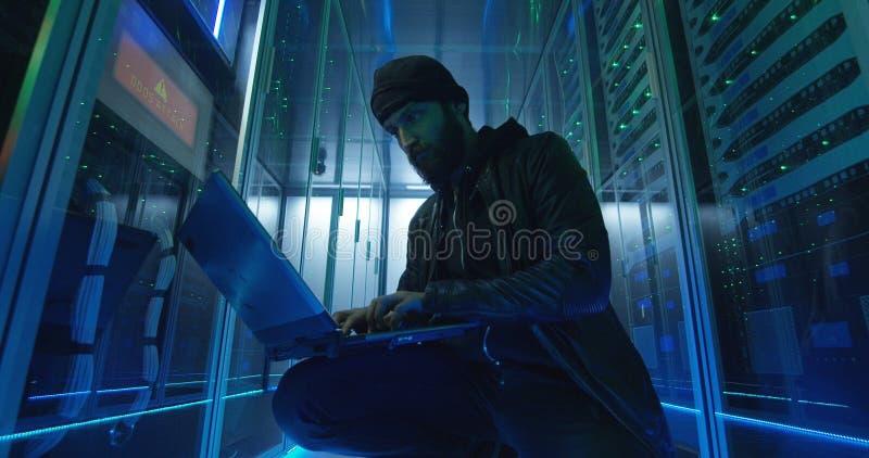 Homem adulto que corta servidores com computador foto de stock