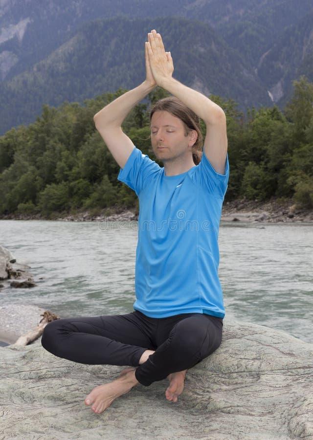 Homem adulto que faz a pose de Namaste fora imagem de stock